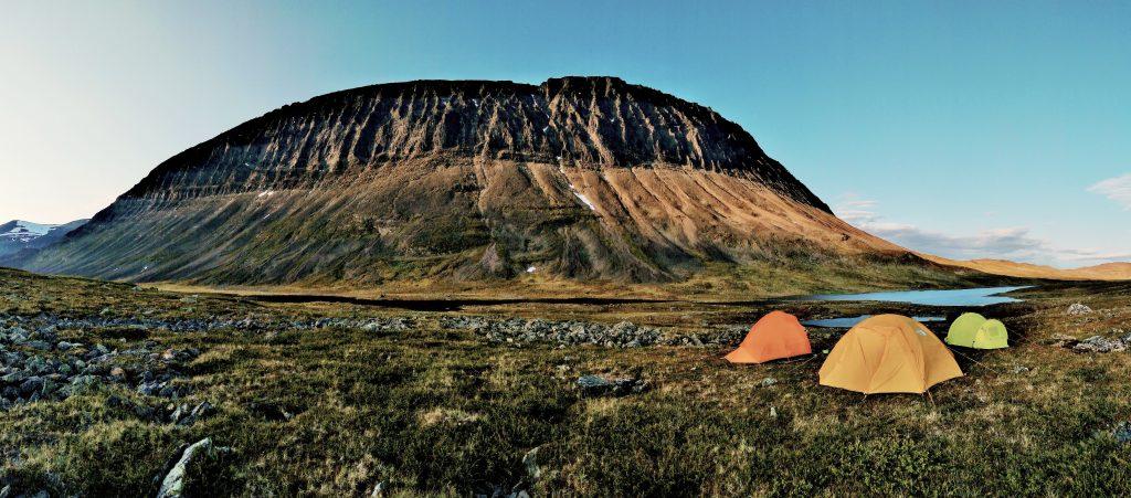 Kolme telttaa pystytettynä vuoristomaisemassa.